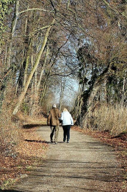 older couple walking hand in hand down trail