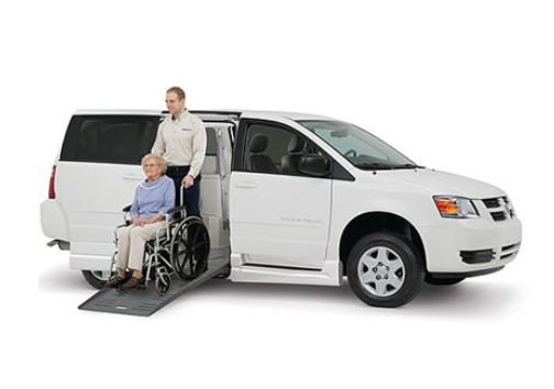 caregiver helping older woman out of wheelchair accessible vehicle
