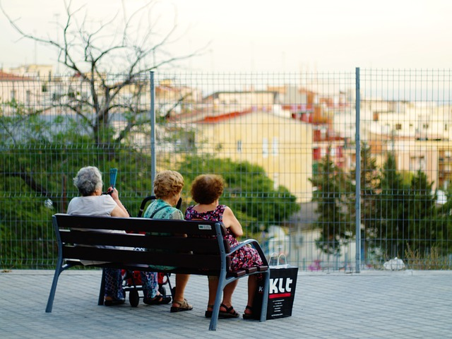three older adults sitting on a bench facing away