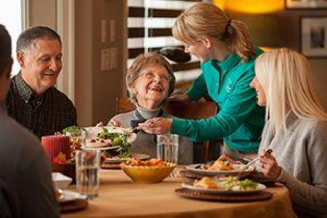 Older woman eating with family