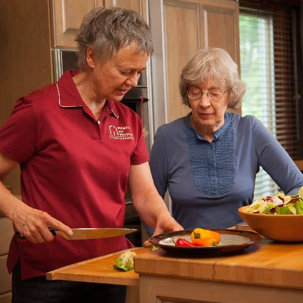 Caregiver cooking with senior